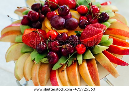 Sliced apples, kiwi, strawberries and cherries lies served on the plate