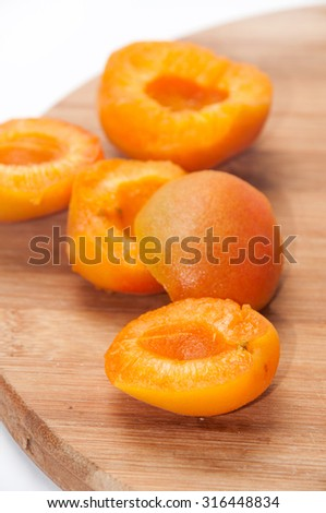 Sliced apricots on the wooden board.