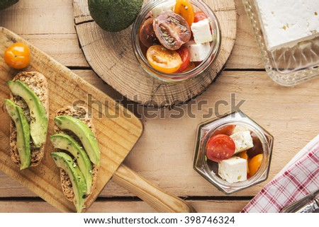 Sliced avocado on toast bread with spices and tomato salad over wooden background - stock photo