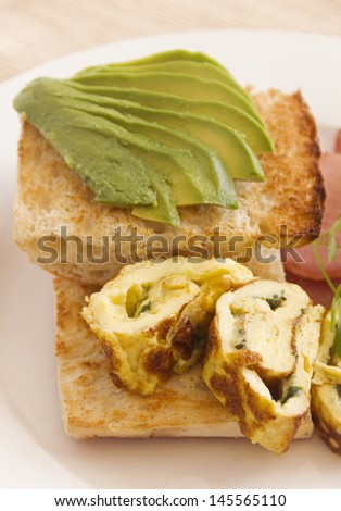 Sliced avocado on toasty Turkish bread with rolled omelette ready to serve. - stock photo