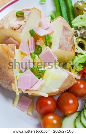 Sliced baked potato with melted cheese and butter with chopped ham and fresh salad - stock photo