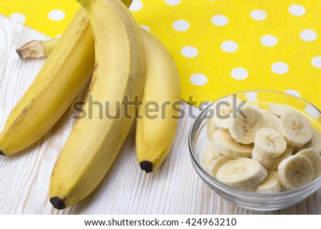 Sliced banana in bowl on white wooden background. - stock photo