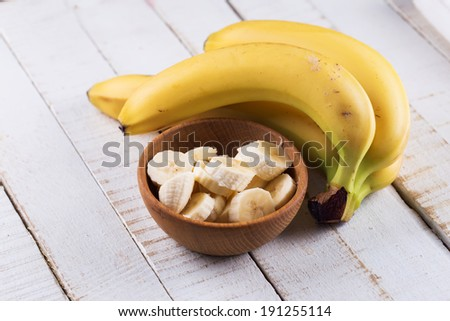 Sliced banana in bowl on white wooden background. Selective focus, horizontal. - stock photo