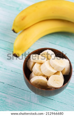 Sliced banana in bowl on  wooden background. Selective focus. - stock photo
