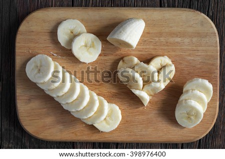 Sliced bananas and shape of hearts on wooden cutting board, top view - stock photo