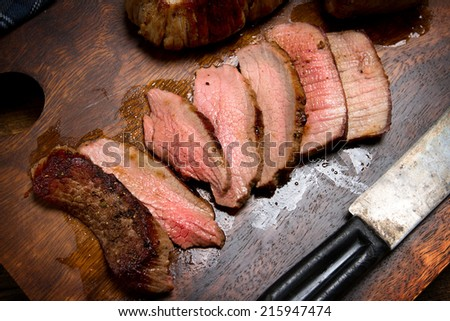 Sliced beef tenderloin on a chopping board - stock photo