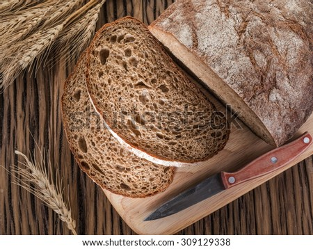 Sliced black bread on the old wooden plank. - stock photo