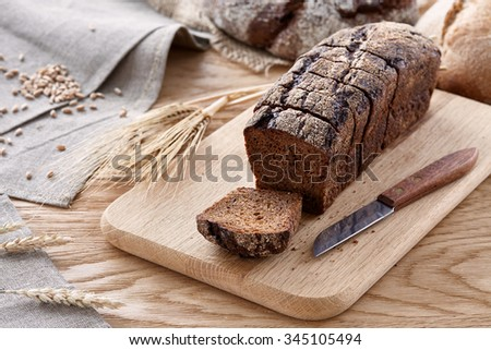 Sliced black rye bread with wheat and rye ears on a wooden table