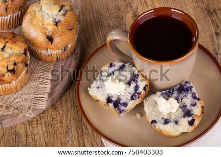 Sliced blueberry muffin and butter with a cup of coffee