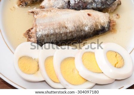 Sliced boiled egg and sardines served on the plate. - stock photo