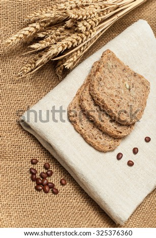 Sliced bread and ears of wheat on canvas background