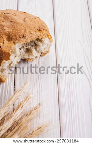 sliced bread and ears of wheat on white painted wooden boards with copyspace food and drink concept  - stock photo