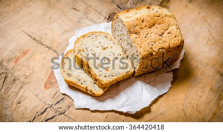Sliced bread on paper. On a wooden table.