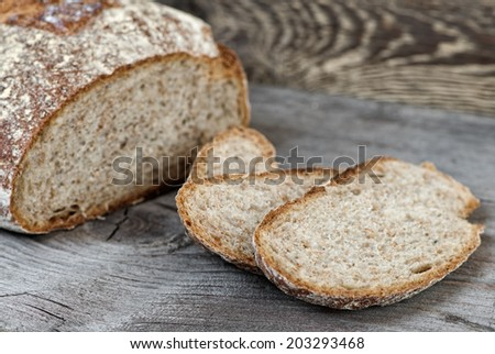 Sliced brown bread on wooden table.