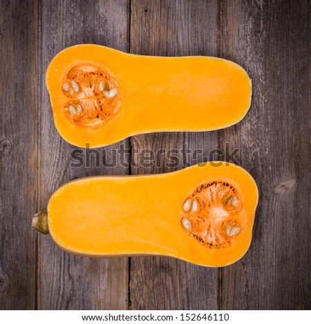 Sliced butternut squash over old wood with intentional vignette - stock photo