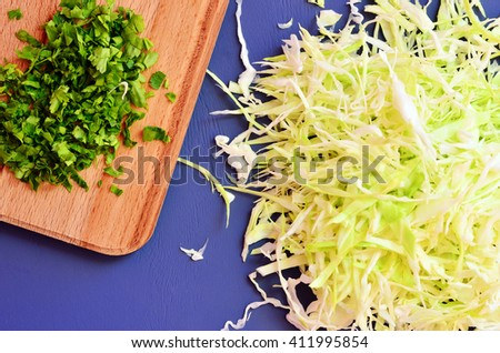 Sliced cabbage on the table next to the chopped parsley - stock photo