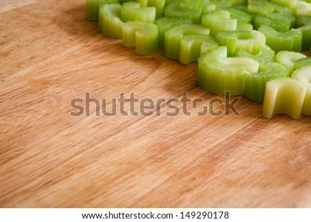 Sliced celery arranged on wooden chopping board - stock photo