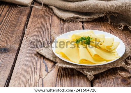 Sliced Cheese on rustic wooden background (close-up shot) - stock photo