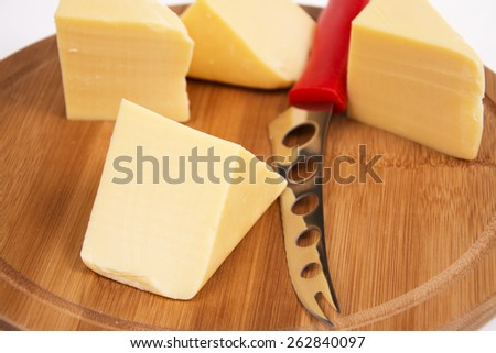 Sliced cheese on the board in the kitchen