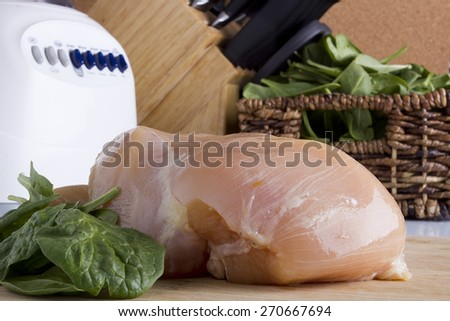 Sliced chicken white meat on a kitchen wooden board.
