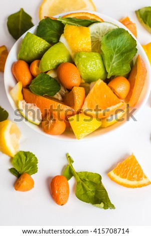 Sliced citrus fruit on the plate. Citrus salad on white background. Top view - stock photo
