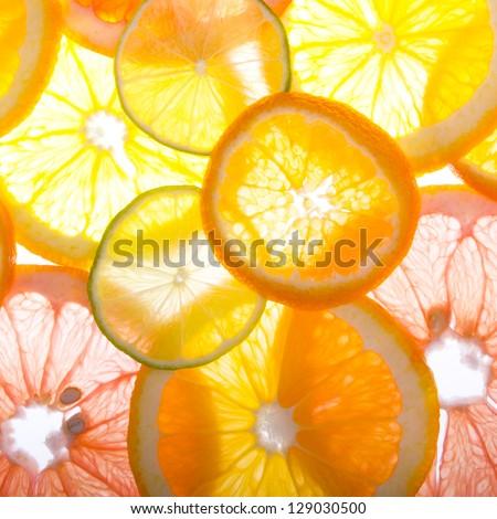 Sliced citrus fruits background - stock photo
