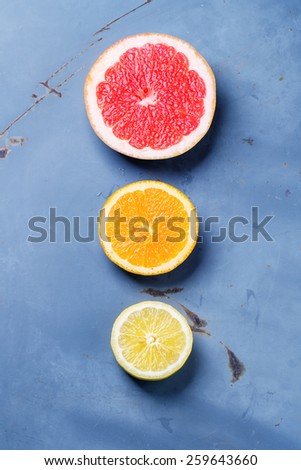 Sliced citrus lemon, orange and grapefruit over blue metal surface. Top view. - stock photo