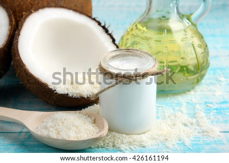 sliced coconut and coconut milk in a small glass jar near oil on blue wooden background
