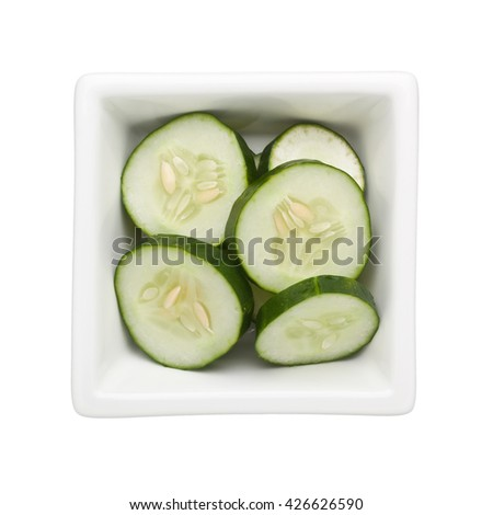 Sliced cucumber in a square bowl isolated on white background