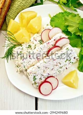 Sliced curd terrine with dill and radishes, green onions, boiled potatoes in a dish, bread, napkin, parsley, lettuce on a light wooden planks on top - stock photo