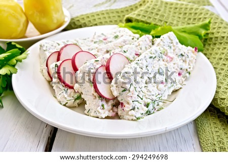Sliced curd terrine with dill and radishes, green onions, salad on a plate, boiled potatoes, napkin, parsley on a light wooden planks - stock photo