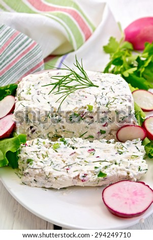 Sliced curd terrine with dill and radishes, green onions, salad on a plate, napkin on a light wooden planks on top - stock photo