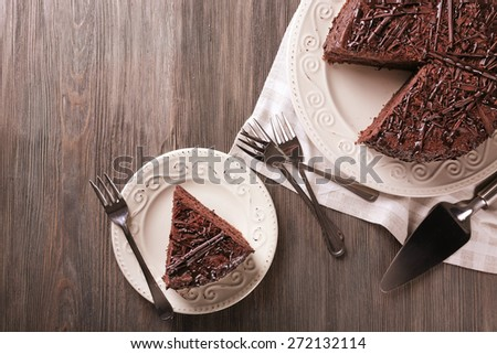 Sliced delicious chocolate cake with cutlery on wooden table background - stock photo