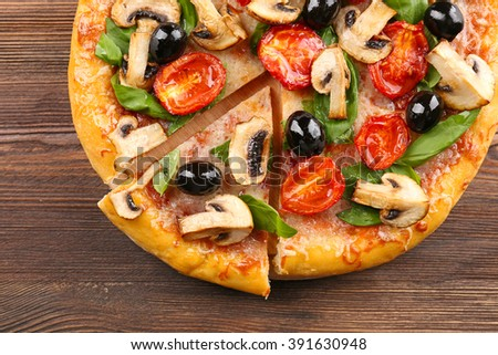 Sliced delicious tasty pizza with vegetables on wooden table - stock photo