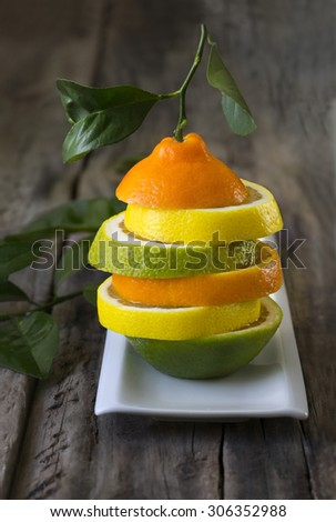 Sliced different citrus fruits stacked in a plate on rustic wooden table top. Stylized fruit. - stock photo