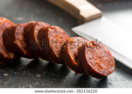 sliced dried sausages on old kitchen table - stock photo