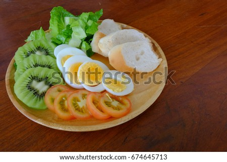 Sliced egg salad serve with vegetable, kiwi, tomato, and crispy bread (on the left)