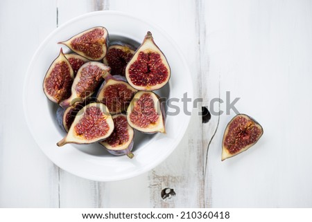 Sliced fig fruits in a glass plate, above view, horizontal shot - stock photo