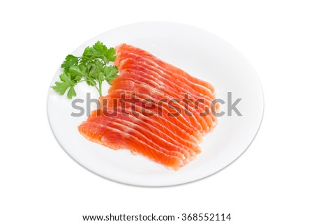 Sliced fillet of salted rainbow trout and a sprig of parsley on a white dish on a light background