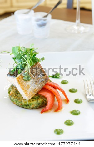 Sliced fish fillet with green salad - stock photo
