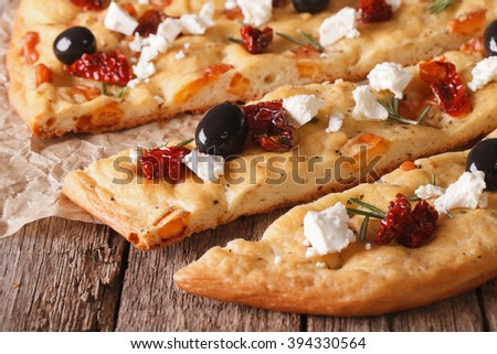 Sliced focaccia with dried tomatoes, feta and olives on the table. macro horizontal