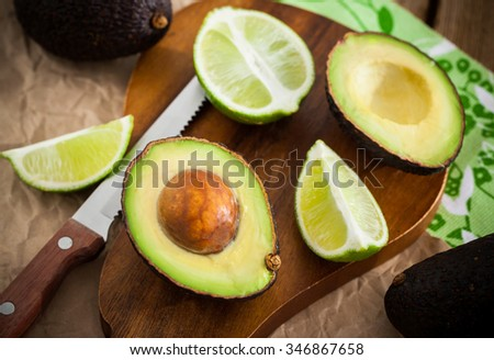 Sliced fresh avocado and lemon lime on cutting board, on wooden background - stock photo