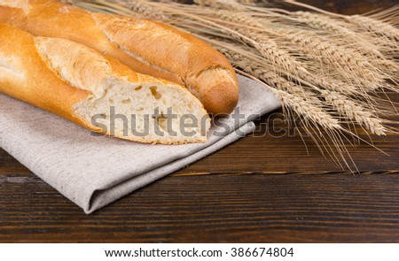 Sliced fresh French baguette cut through to show the texture alongside fresh ripe ears of wheat on a rustic wooden table, close up view - stock photo