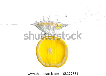 Sliced fresh lemon falling into the water with a splash on a white background closeup