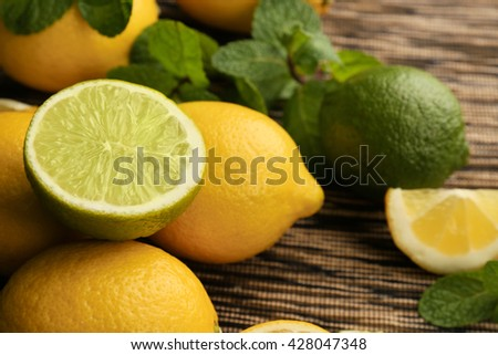 Sliced fresh lemon with green leaves on wooden table closeup - stock photo