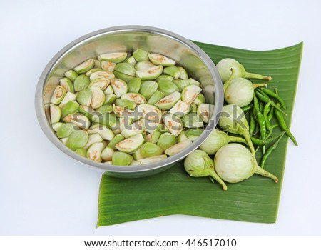 Sliced fresh organic eggplant in water and green chilli on banana leaf against white background - stock photo