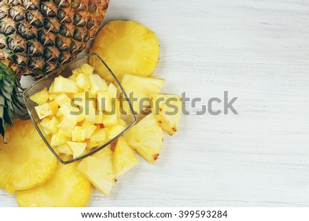 Sliced fresh pineapple in glass saucer on wooden table, top view - stock photo
