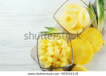 Sliced fresh pineapple in glass saucers on wooden table, top view - stock photo