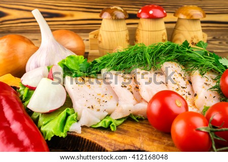 Sliced fresh pork lard, fresh produce, greens, vegetables on the wooden board, close-up, selective focus - stock photo