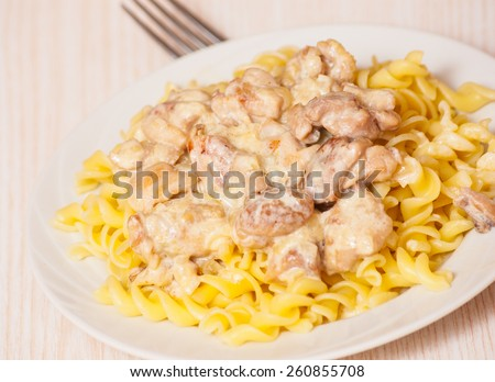 Sliced fried chicken in a creamy sauce. with fusilli pasta - stock photo